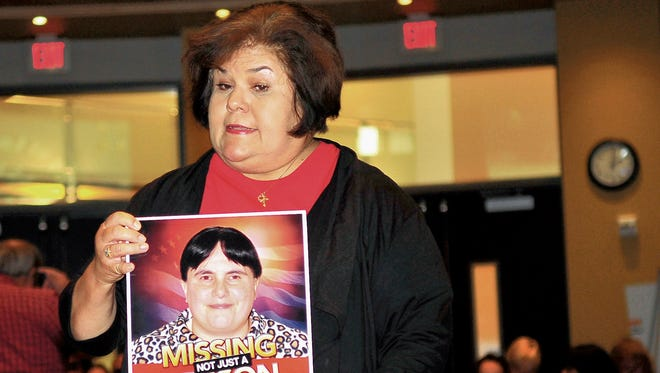 Castrejon family friend Liz Ramirez-Valdez shows a picture of Janet Castrejon, who went missing three months ago, to members of the Las Cruces City Council on Monday at city hall.