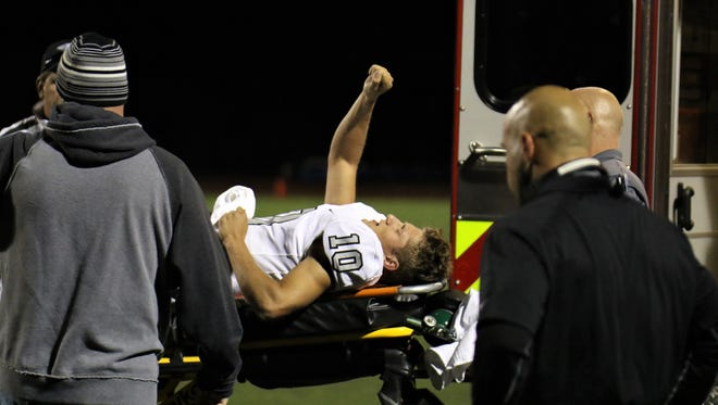 Plymouth senior quarterback Zach Beadle (10) gives a sign of encouragement to the crowd as he is moved into an ambulance Friday, Sept. 29.