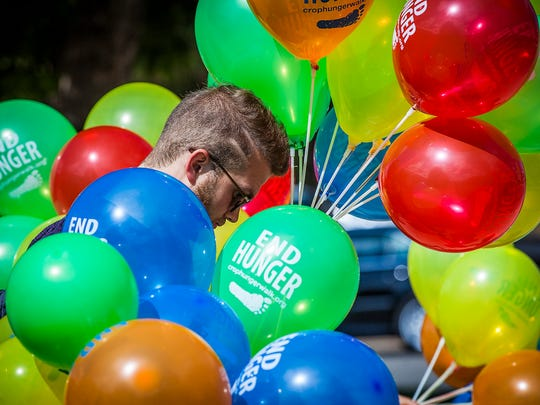 A volunteer holds balloons for walkers at College Avenue