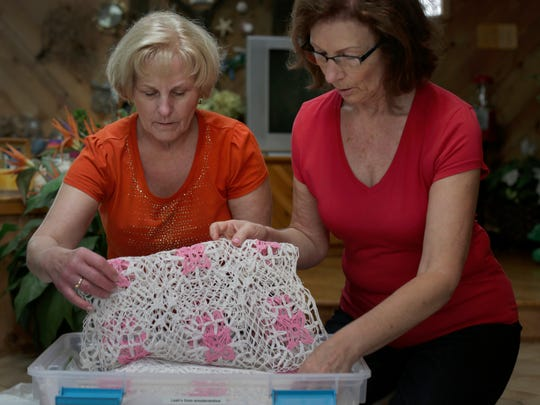 Sisters Judy Juengel, left, and Ruthann Bettcher look through items that their mother Viola Kogelman made by hand for her family and grandchildren Tuesday, Sept. 29, 2015, at Bettcher's home. Hospice workers in a program called Holding Hands Forever took a photo of the daughters holding their mother's hands before she died. Viola Kogelman worked with her hands her whole life.