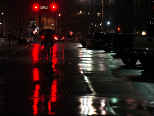 A couple walks through the rain in downtown Montgomery,