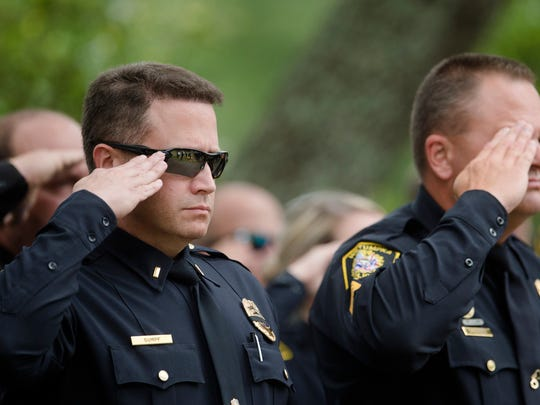 Wetumpka police officers salute during the playing of Taps at the burial ceremony for Wetumpka Police Chief Danny Billingsley on Monday, May 21, 2018, at Greenwood Cemetery in Montgomery, Ala.