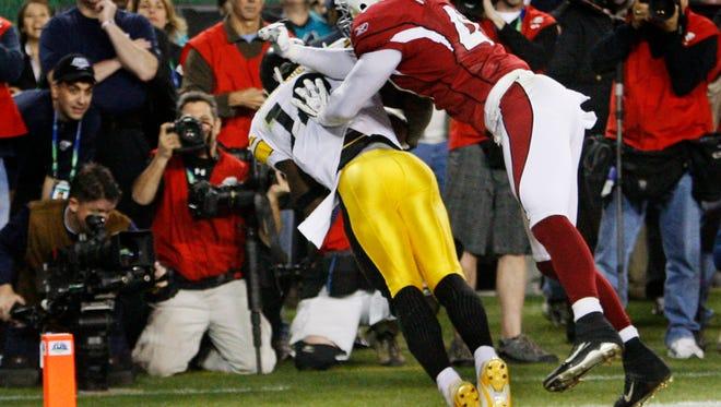 Steelers wideout Santonio Holmes scores the winning touchdown past Arizona Cardinals Aaron Francisco #47 during Super Bowl XLIII at Raymond James Stadium in Tampa, Florida.