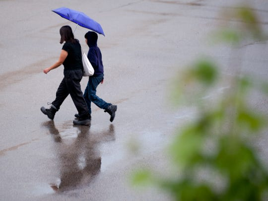 A woman and a young boy walk along in the rain across Capitol Avenue in Lansing on Thursday, July 21, 2016. Storms moved through the area during the afternoon. Temperatures reached into the 90s. The National Weather Service in Grand Rapids issued a heat advisory, effective from 1 p.m. Thursday to 7 p.m. Friday.
