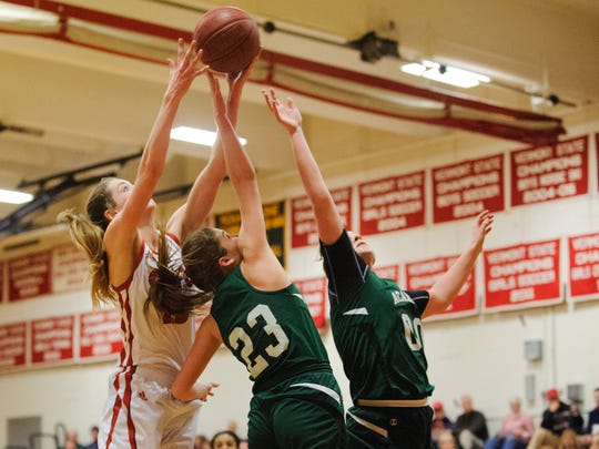 CVU's Shannon Loiseau (23) leaps over St. Johnsbury's Neva Bostic (23) and Saleena Porter (00) to grab the rebound during the girls basketball game between the St. Johnsbury Hilltoppers and the Champlain Valley Union Redhawks at CVU High School on Tuesday night January 9, 2018 in Hinesburg.