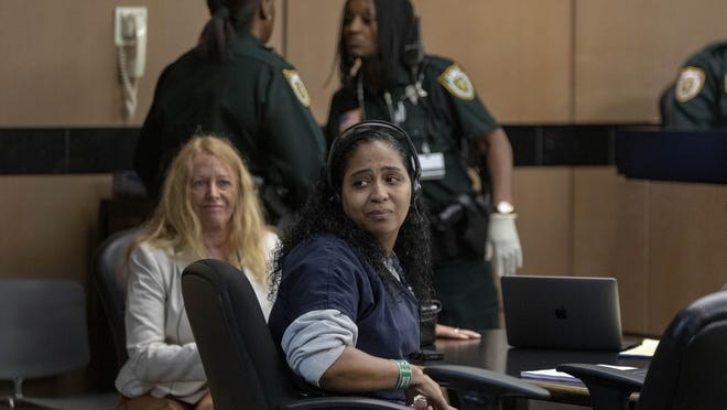 Interpreter Susan Dix-Barboza, left, watches as Rafaelle Sousa looks back at her family during a hearing on Jan. 13, 2020, in West Palm Beach. Sousa is accused of leaving her newborn baby in a dumpster.
