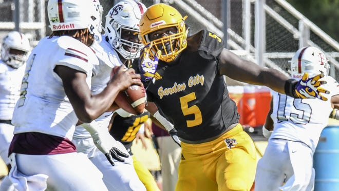 Garden City Community College defensvie end Ali Gaye, right, breaks through the Fort Scott offensive line and zeroes in on quarterback Rayvon Bartlett Jr. for a sack last season at Broncbuster Stadium. GCCC has set dates for athletes competing in the upcoming school year to check in.