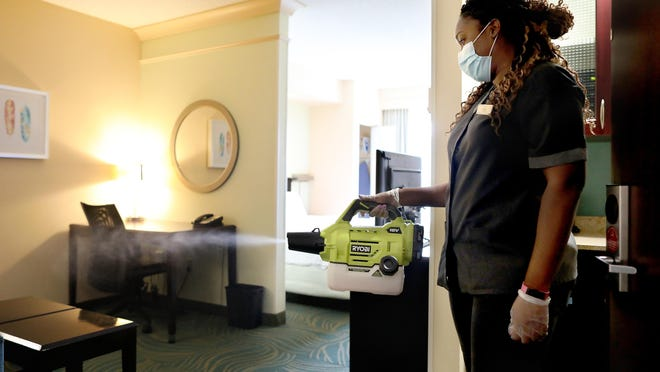 Maria Wali-Uddin, a member of the housecleaning staff, uses a handheld electrostatic defogger to sanitize a room at the SpringHill Suites in Gainesville Thursday. As part of the Safe Stay Pledge, some 28 hotels in the Gainesville area have agreed to a set of guidelines for keeping their hotels clean and safe.