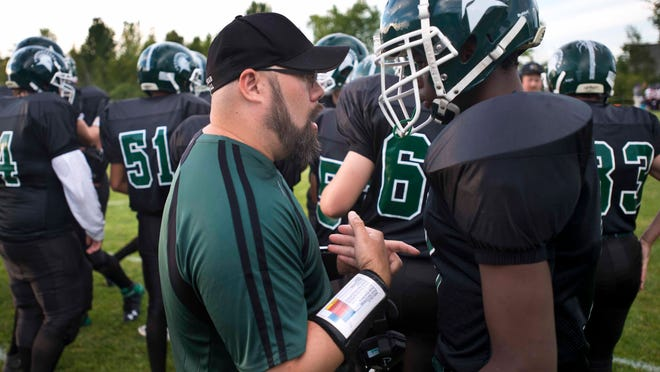 Winooski assistant coah Joe Bougor (left) has a word with Abdu Arbow before the Spartans' game against Oxbow in Winooski on Friday, August 29, 2014.
