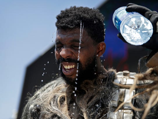Xaviere Coleman pours water over his head to cool off