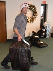 Mark Fangmeyer helps to round up bags of gifts for families during the Civic Concern holiday distribution party.