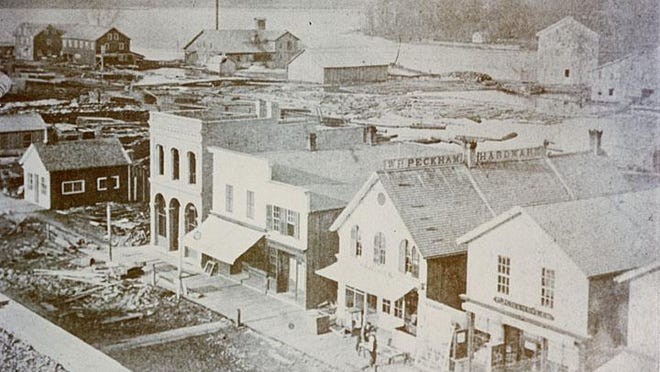 Downtown Neenah's Wisconsin Avenue is shown in this 1870s photograph. The W. P. Peckham Hardware store can be seen and in the background is the Fox River and Little Lake Butte des Morts.
