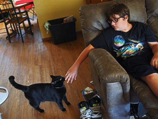 DJ Hilfers, 14, plays with his cat Shadow while watching