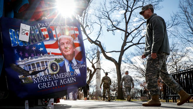 Military personnel walk along the National Mall in Washington on Wednesday alongside vendors selling President-elect Donald Trump merchandise ahead of Friday's presidential inauguration.