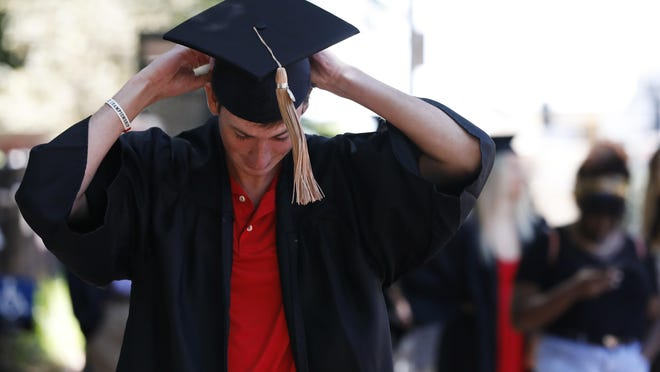 Graduates line up to take photos at the University of Georgia Arch in downtown in Athens, Ga, on May 7, 2020.