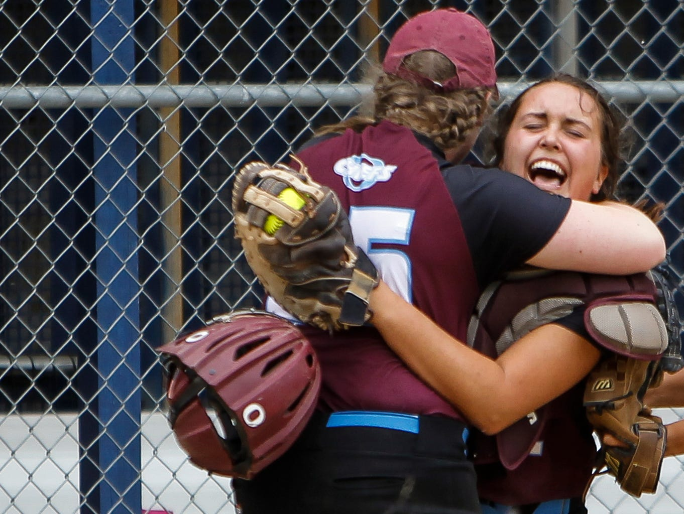 Okemos pitcher Sally Patterson and catcher Kate Buckland hug after the Chiefs beat St. Johns 3-1 to win the Division 1 softball final in East Lansing.