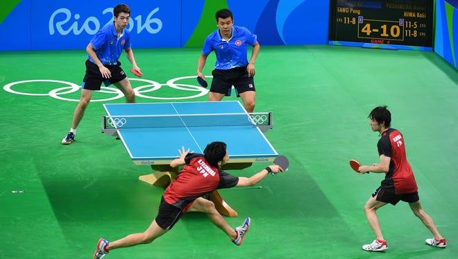 Peng Tang (HKG) and Kwan Kit Ho (HKG) take on Koki Niwa (JPN) and Maharu Yoshimura (JPN) in a men's team table tennis match at Riocentro - Pavilion 3 during the Rio 2016 Summer Olympic Games.