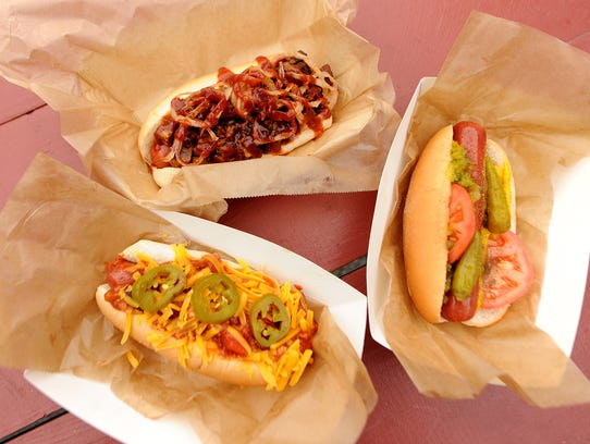 A trio of hot dogs including Chili Dog, left, Brisket Dog, top, and Philly Dog at the Indianapolis Motor Speedway, Friday, May 9, 2014, in Indianapolis.
