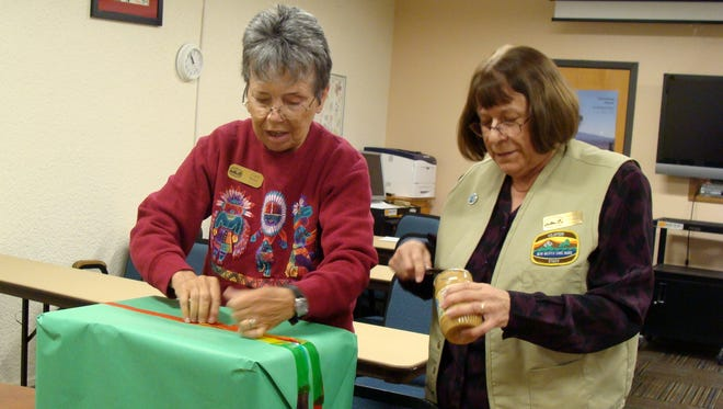 Sandra Cosand, right, and Carol Belski used peanut butter to seal Maggie's gift on Thursday.