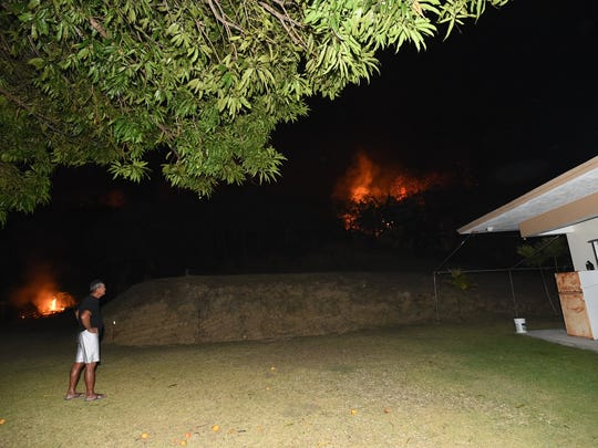 Ken Cruz, 72, watches flames from a grass fire subside near his son's property in Merizo on Feb. 19, 2018. Guam Fire Department units arrived on the scene earlier in the evening, according to Cruz, who noticed the area ablaze around 5 p.m.