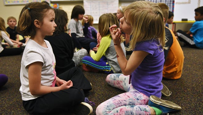 Chalease Kenyon, left, and Harper Hartmann-Johnson, both 2nd-graders, talk with each other while working on an assignment during 2nd-grade Spanish immersion teacher Amanda Valbuena's class Tuesday, April 19, 2016, at the Instructional Planning Center in Sioux Falls.