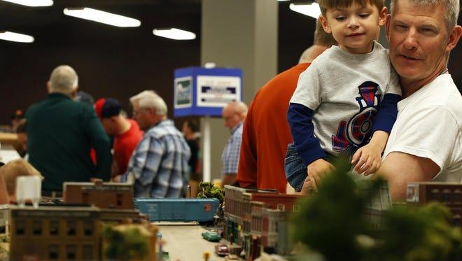 Steve Wagner and Jaxon Martz, 3, watch a model train go through a layout during last year's Ozarks Model Railroad Association Annual Spring Train Show.