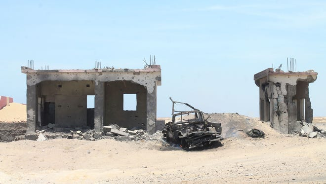 The wreckage of a car and damaged buildings are seen in Ras Imran, west of the port city of Aden, following Saudi air strikes against Huthi rebels on April 16, 2015.