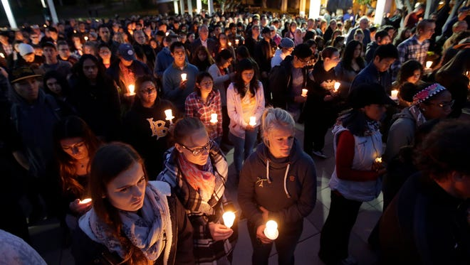 Well-wishers hold up candles during a memorial service for California State Long Beach student Nohemi Gonzalez on Sunday, Nov. 15, 2015 in Long Beach, Calif., who was killed at restaurant in Paris on Friday night during the terrorist attacks. (AP Photo/Chris Carlson)