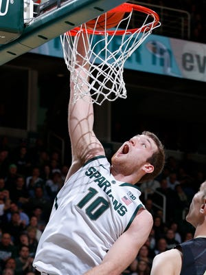 Michigan State's Matt Costello (10) dunks against Purdue's Isaac Haas during the second half of an NCAA college basketball game, Wednesday, March 4, 2015, in East Lansing, Mich. Michigan State won 72-66.