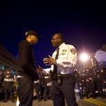 A Baltimore police captain tries to calm a protester Tuesday night.