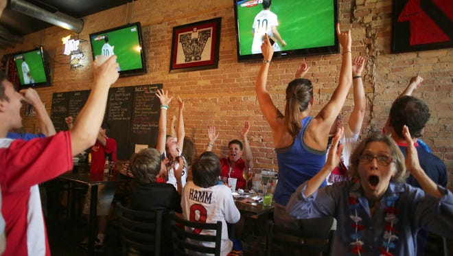 Soccer fans Morgan Ansems, left center, and Dana Koch, right, cheer a goal Sunday during a Women's World Cup viewing party at Greene's Pour House in Neenah.