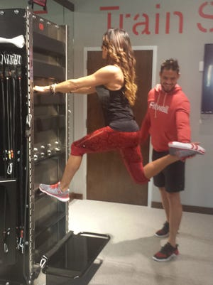 Manager Amy Goble demonstrates a Fitwall exercise with assistance from head coach Zach Nichols.