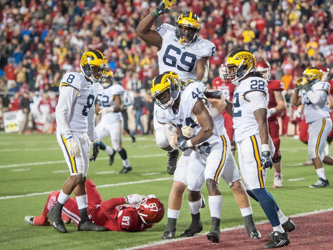Michigan safety Delano Hill (44) is mobbed by his teammates