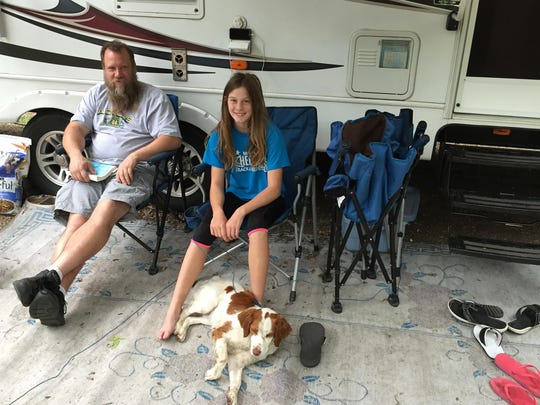 C.J. Mortier, an HVAC installer from Marshall, sat outside the family's camper at Sibley State Park with daughter Jenna, 13, and their dog, Sadie.