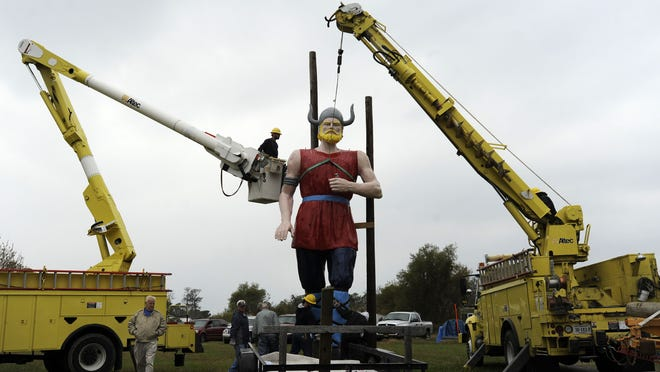 A crew from ANEC hoists the Viking on Chincoteague, Va. on Wednesday, Oct. 23, 2013. The Viking, a mainstay of Ridge Road near the site of the annual Chincoteague Pony Swim, was blown over during Hurricane Sandy last year. The Chincoteague Kiwanis Club had the Viking repaired and repainted.