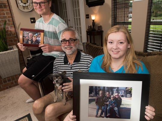 Bradley Hill, left, and his sister, Asheton Hill, right, hold photos of some of their family's favorite memories. Their stepfather, Brian LeBlanc, center, has been diagnosed with early-onset Alzheimer's disease.