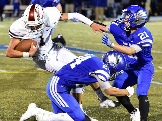 Milford's Aiden Warzecha (with ball) is brought down by Lakeland's Dylan Kutzleb (bottom) and Joe Rzeppa (right).