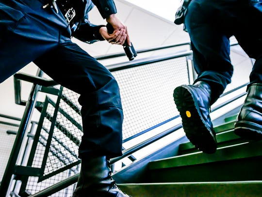 First responders run up a staircase to meet and neutralize