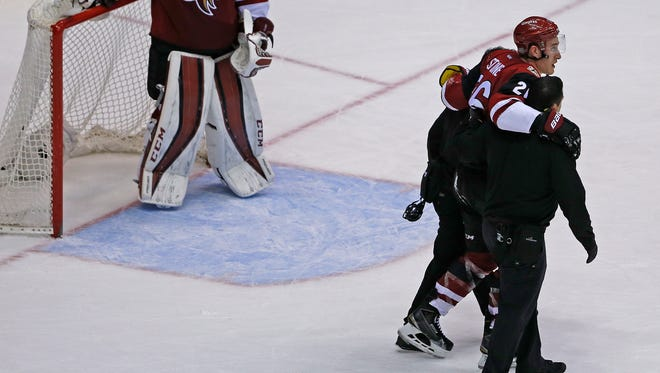 Coyotes' Michael Stone (26) is helped off the ice after an injury to his left leg against the Flyers during the second period at Gila River Arena on Saturday, March 26, 2016.