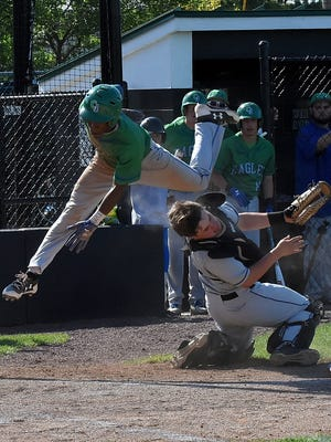 Chaminade's AJ Solomon leaps and lands a knee into CHCA catcher Oakley Tippen on his way to Home at the Division II region championship at Mason High School, May 25, 2018.