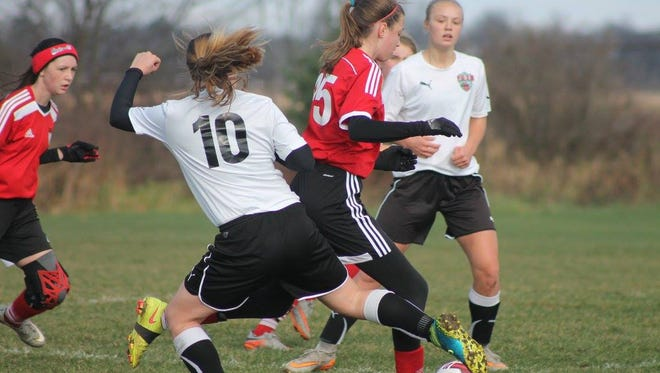 Madison Simpson (#10) tries to steal the ball from the opponent in a Premier league match. Abby Gemza (back) looking on.
