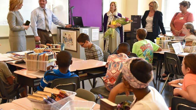 In this Aug. 30, 2016 photo, Wicomico County 2016-2017 Teacher of the Year Christy Briggs poses with a bouquet of flowers and in royal attire after a surprise announcement in her sixth-grade classroom that she is a finalist for 2016-2017 Maryland Teacher of the Year.  In front to greet Briggs are from left, Superintendent  Donna Hanlin; Director of Secondary Education Micah Stauffer; finalist Christy Briggs; Bennett Middle Principal Liza Hastings; and Supervisor for Middle School English Language Education Supervisor Paige Greenwood.