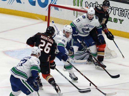 The shot by Anaheim Ducks defenseman Brandon Montour (26) makes its way through a crowd of Vancouver Canucks including center Bo Horvat (53) for the goal during the first period of an NHL hockey game in Anaheim, Calif., Wednesday, March 14, 2018. (AP Photo/Reed Saxon)