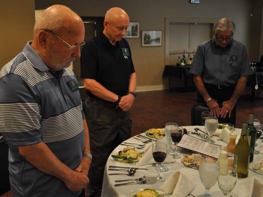 "The Order of Daedalians 60th Flight members (from left) Berchman Richard, Flight Commander Mike Carlin and Adjutant Joe Lodrige pause for a moment of silence to honor their departed ""brother and sister"" pilots."