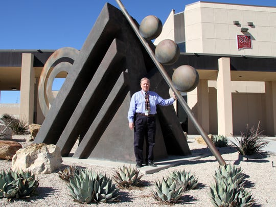 Mike Cleary poses with an outdoor sculpture he helped to obtain as part of the university's 50th anniversary celebrations in 2000.