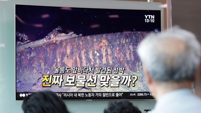 People watch a TV screen showing the news program reporting about a sunken Russian warship at the Seoul Railway Station in Seoul, South Korea, on July 19, 2018.