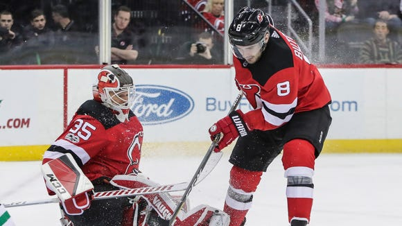 New Jersey Devils defenseman Will Butcher (8) clears the puck in front of goalie Cory Schneider (35) during the first period against the Dallas Stars at Prudential Center.