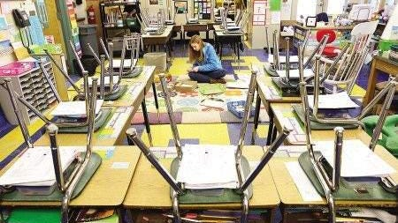 In this 2014 file photo, Raina Martinec, a third-grade teacher at the Coastal Ridge Elementary School in York, Maine, prepares for sudents in the art room, after a frozen water pipe burst. The school will be closed Thursday, Oct. 8, 2020, after a positive COVID-19 case was identified in someone with ties to the school.