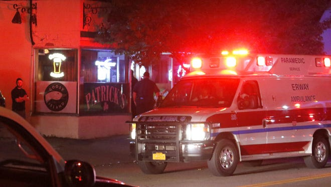 An ambulance drives away from Patrick's bar on College Avenue following a shooting there early Thursday.