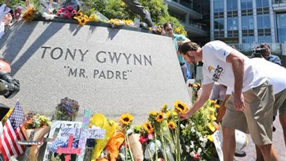 """Members of the San Diego Chargers place flowers at the base of the Tony Gwynn """"Mr. Padre"""" statue Monday in San Diego. Gwynn, an eight time National League batting champion with the San Diego Padres and a member of Baseball Hall of Fame, died Monday from cancer. He was 54. (AP Photo/Lenny Ignelzi)"""